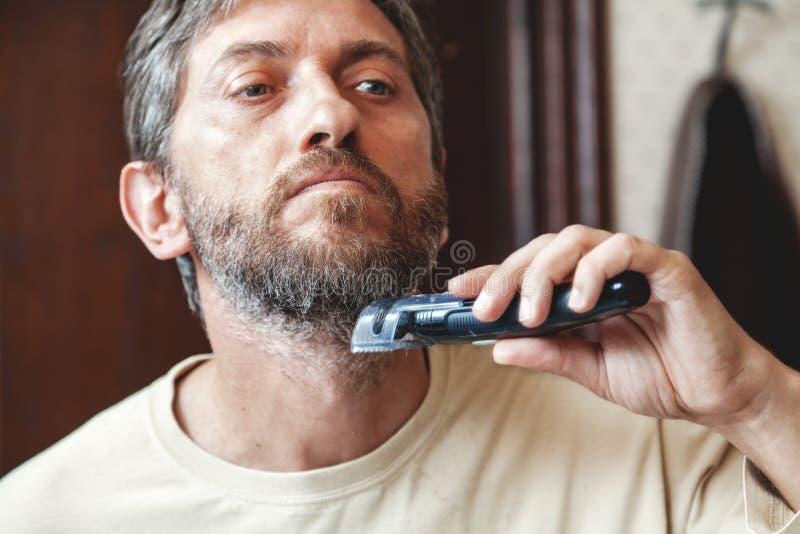 Het verzorgen baard met de grijze close-up van de haarsnoeischaar royalty-vrije stock afbeelding