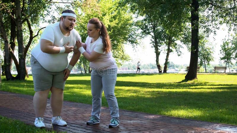 Het vette mannetje voelt hartpijn terwijl het aanstoten, zwaarlijvig meisje die hem, vriendensteun helpen stock afbeelding