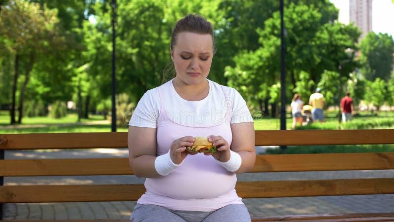 Het vette meisje worstelt met verleiding om hamburger te eten, ongezonde kost, geen wilskracht verkiezen stock afbeeldingen