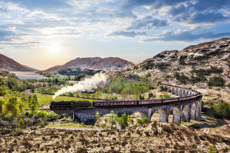 Het Viaduct van de Glenfinnanspoorweg in Schotland met de Jacobite-stoomtrein tegen zonsondergang over meer stock afbeeldingen