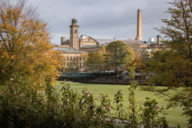 Het Victoriaanse modeldorp van Saltaire glimpsed door de bomen stock foto