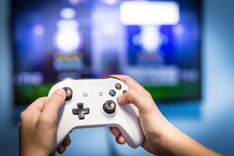 Het videogokken en het spel spelen op TV-het gamepad van de pret gamer holding en controlemechanisme videoconsole die en met het  royalty-vrije stock afbeeldingen