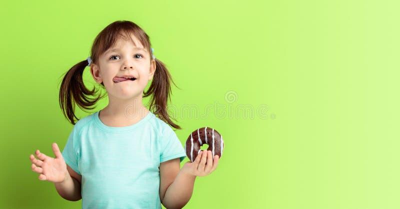 Het vier-jaar-oude meisje eet doughnut royalty-vrije stock afbeelding