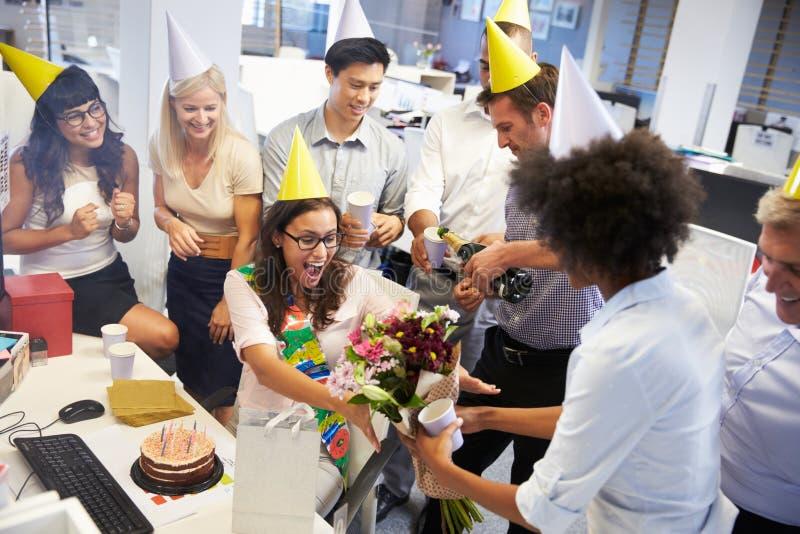 Het vieren de verjaardag van een collega in het bureau stock fotografie