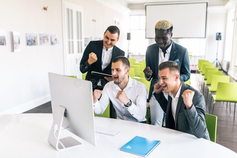 Het vieren succes Groep jonge bedrijfs hun wapens opheffen en mensen die gelukkig terwijl samen het rondhangen van het bureau kij stock afbeelding