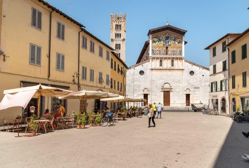 Het vierkant van San Frediano met mensen die van de openluchtbar en de meningen van de Basiliek van San Frediano in oude stad Luc royalty-vrije stock afbeeldingen