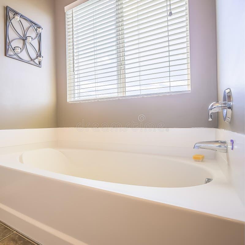 Het vierkante binnenland van de Huisbadkamers met badkuip voor het venster met zonneblinden royalty-vrije stock afbeelding