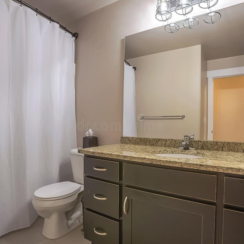 Het vierkante de de eenheidstoilet en handdoek van de kaderijdelheid haken tegen de witte muur van een goed aangestoken badkamers royalty-vrije stock foto's