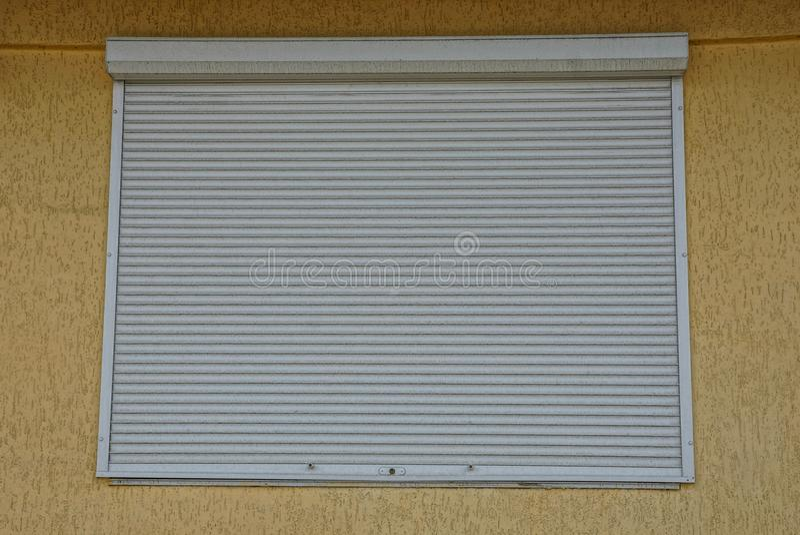 Het vierkante die venster door grijze jaloezie op een muur wordt gesloten royalty-vrije stock foto's