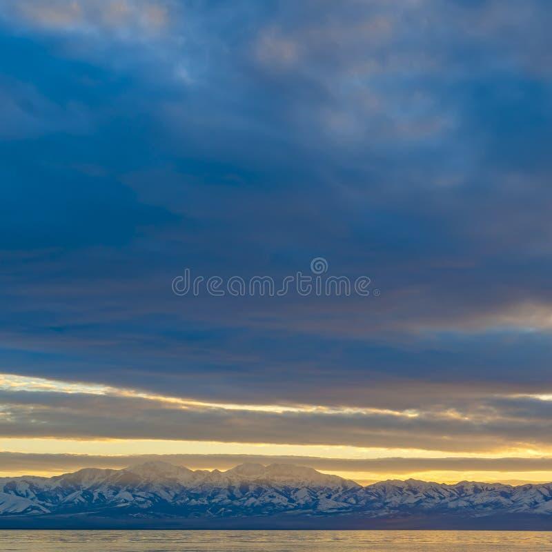 Het vierkante kader Toneelpanorama van een meer en een sneeuw dekte berg onder een opvallende bewolkte hemel af royalty-vrije stock afbeelding