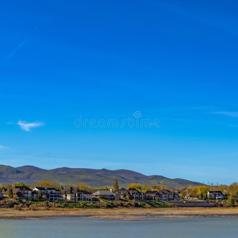 Het Vierkante Panorama van het kaderkader van mooie huizen voor een meer dat op de blauwe hemel wijst stock afbeeldingen