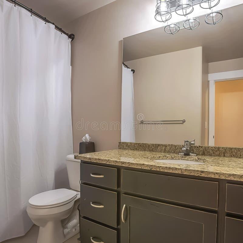 Het vierkante toilet en de handdoek van de Ijdelheidseenheid haken tegen de witte muur van een goed aangestoken badkamers vast royalty-vrije stock afbeelding