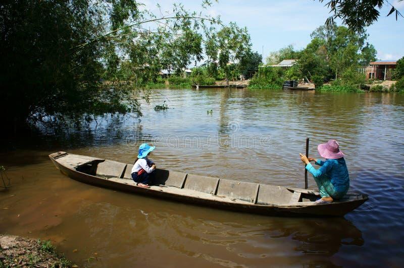 Het Vietnamese meisje van het vrouwenvervoer gaat naar school door houten boot royalty-vrije stock afbeelding