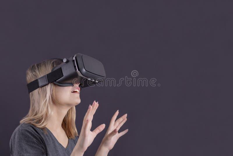 Het virtuele meisje van werkelijkheidsglazen in glazen van virtuele werkelijkheid is verrast stock fotografie