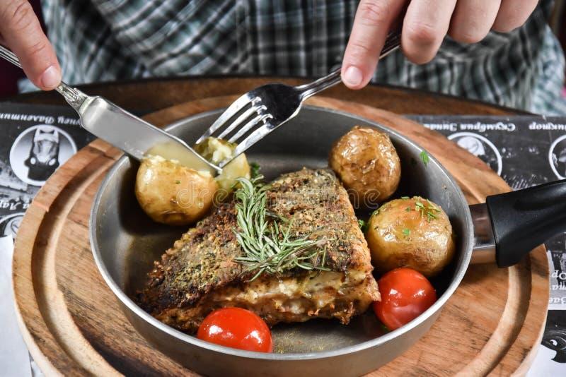 Het visrestaurant, gefrituurde vis, mannelijke handen, de man eet gefrituurde vis, gefrituurde vis en aardappel, gekookt met aard royalty-vrije stock foto's