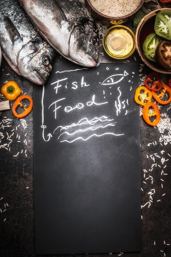 Het vissenvoedsel op zwart bord met ruwe dorado vist en gezonde groenteningrediënten en rijst, hoogste mening royalty-vrije stock fotografie