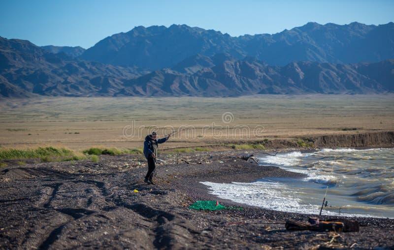 Het visserssilhouet bij de controle vislijn van de zonsondergangvisser en het duwende aas op de staaf, bereiden zich voor en werp stock foto