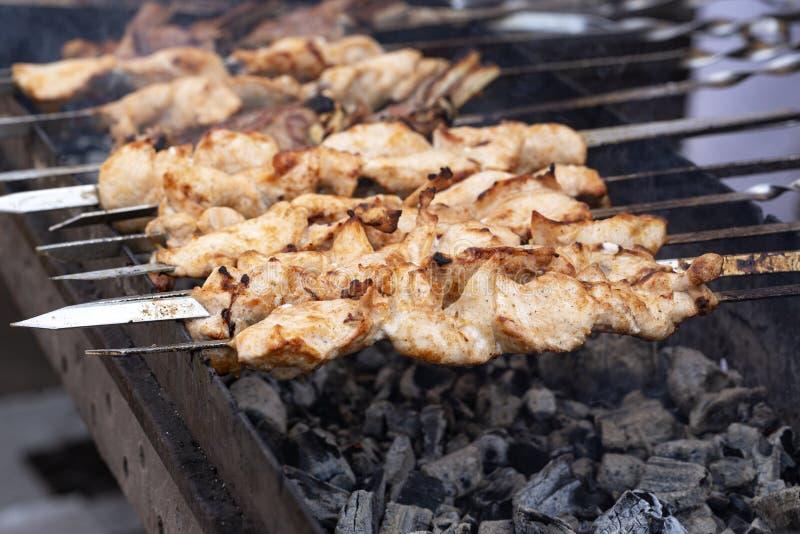 Het vlees is geroosterde vleespennen op een barbecuegrill Heerlijke bbq kebab die bij de open grill, openluchtkeuken roosteren Vo stock afbeeldingen