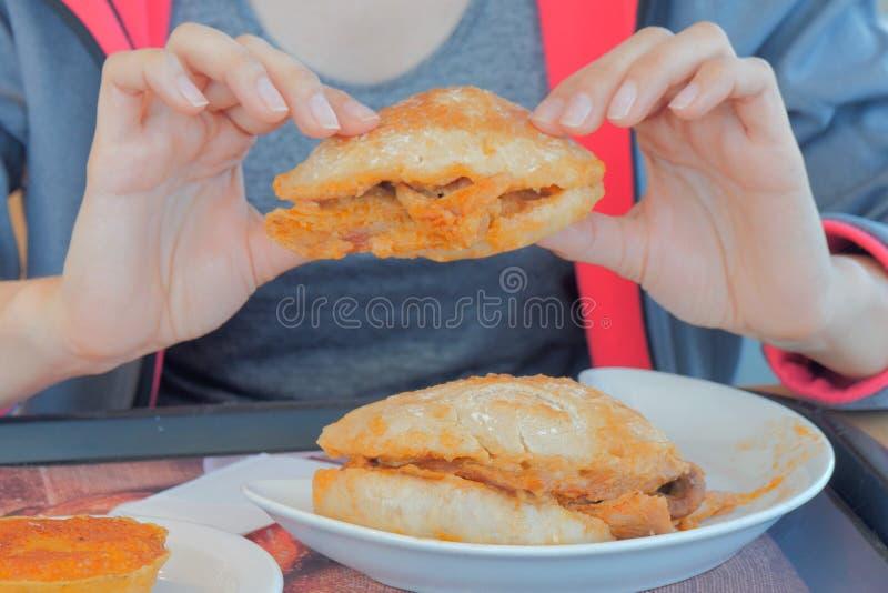 Het vleessandwiches van de vrouwenholding in handen en het gaan eten royalty-vrije stock fotografie