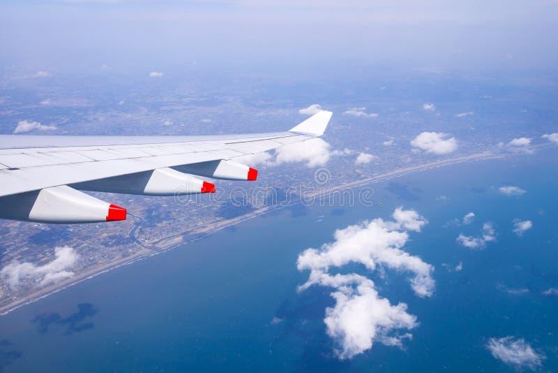 Het vliegen in blauw hemel en overzees strand en Vleugel van vliegtuig met hemel royalty-vrije stock afbeeldingen