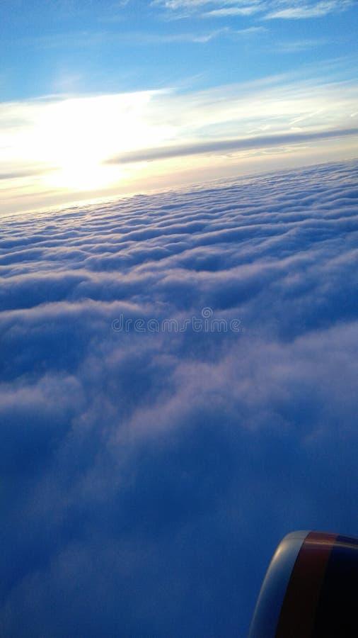 Het vliegen over de wolken bij zonsondergang stock afbeelding