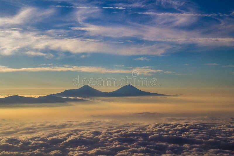 Het vliegen over wolken en bergen royalty-vrije stock afbeelding