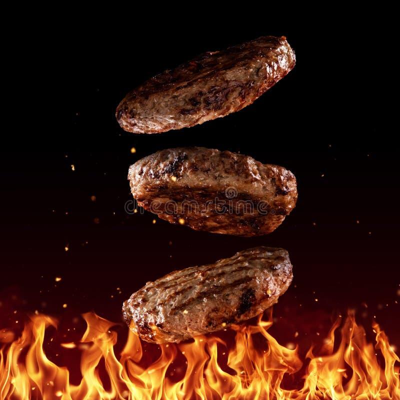Het vliegen rundvlees fijngehakte hamburgerstukken op zwarte stock afbeelding