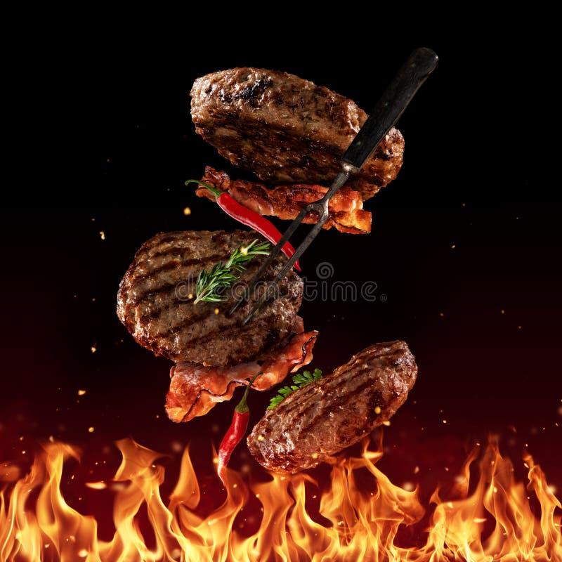 Het vliegen rundvlees fijngehakte hamburgerstukken op zwarte stock afbeeldingen