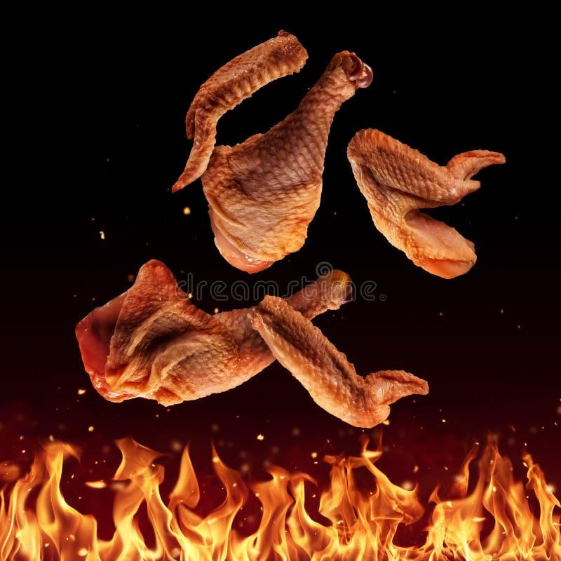 Het vliegen ruwe kippenstukken boven grillvlammen royalty-vrije stock fotografie