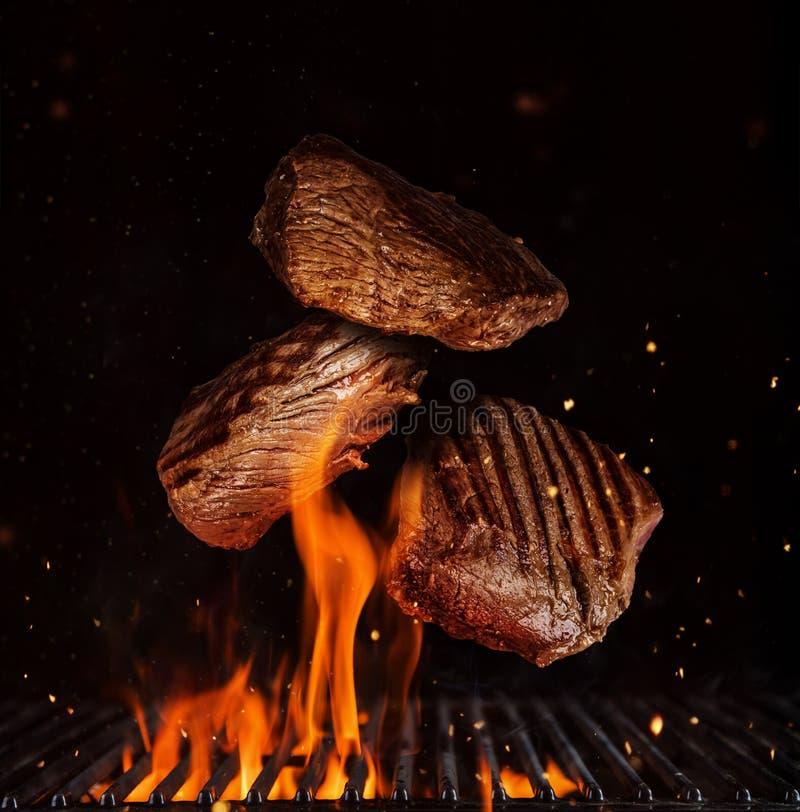 Het vliegen stukken lapjes vlees van het rundvleesachterdeel op zwarte stock fotografie