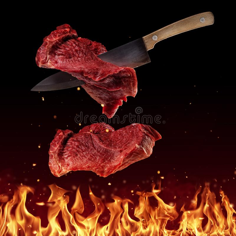Het vliegen stukken lapjes vlees van het rundvleesachterdeel op zwarte stock afbeeldingen