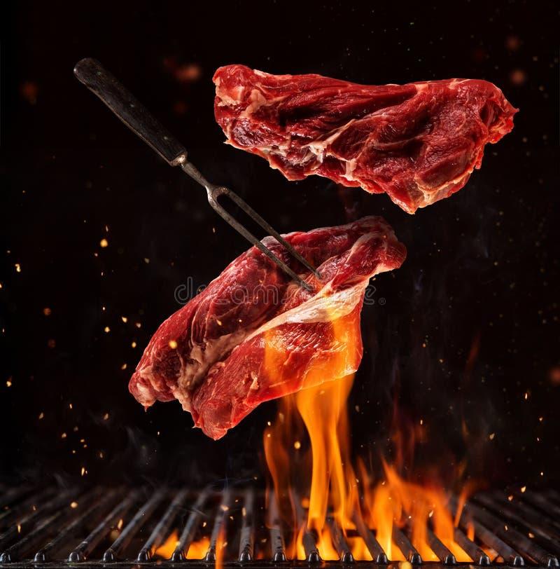 Het vliegen stukken rundvleeslapjes vlees op zwarte royalty-vrije stock foto