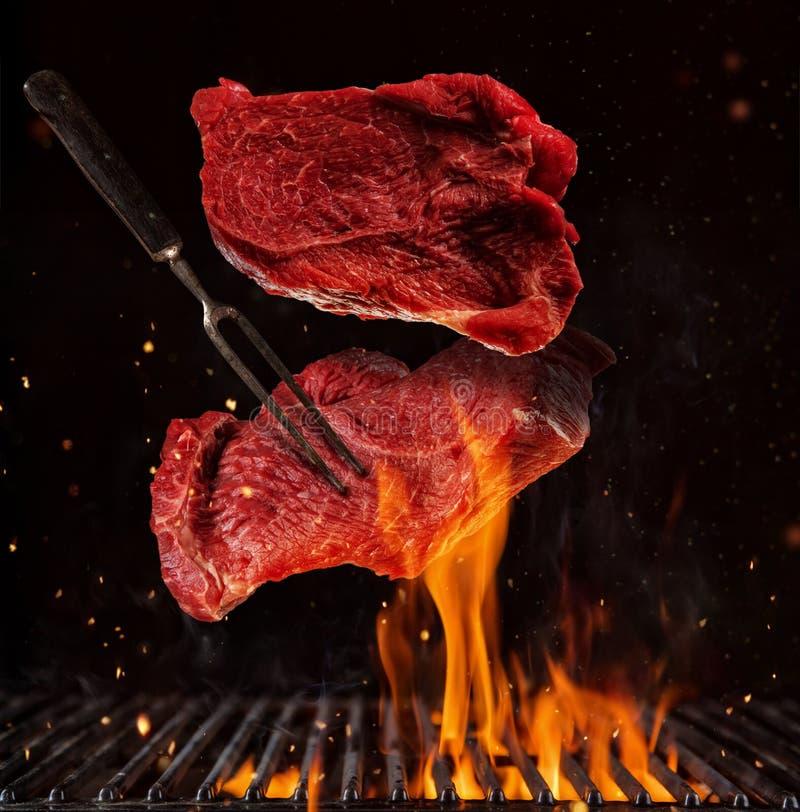 Het vliegen stukken rundvleeslapjes vlees op zwarte royalty-vrije stock foto's