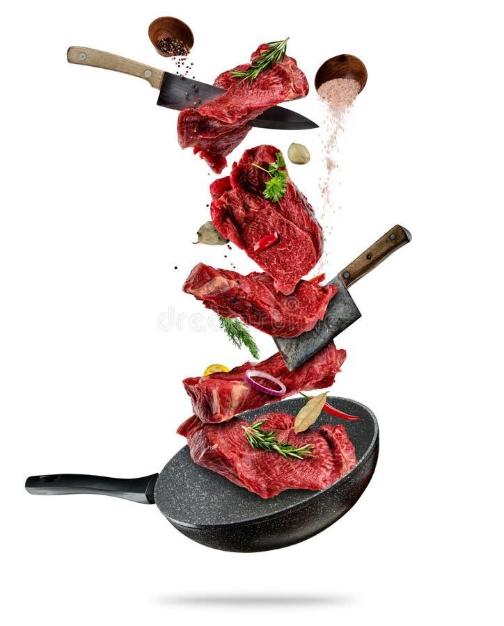 Het vliegen stukken rundvleeslapjes vlees van pan op witte achtergrond royalty-vrije stock foto's