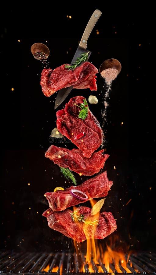 Het vliegen stukken ruwe rundvleeslapjes vlees van grillnet op zwarte backgr stock foto
