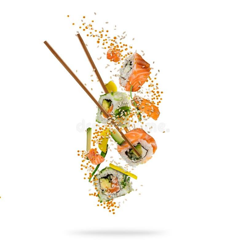Het vliegen stukken sushi met houten die eetstokjes, op whit worden gescheiden royalty-vrije stock afbeeldingen