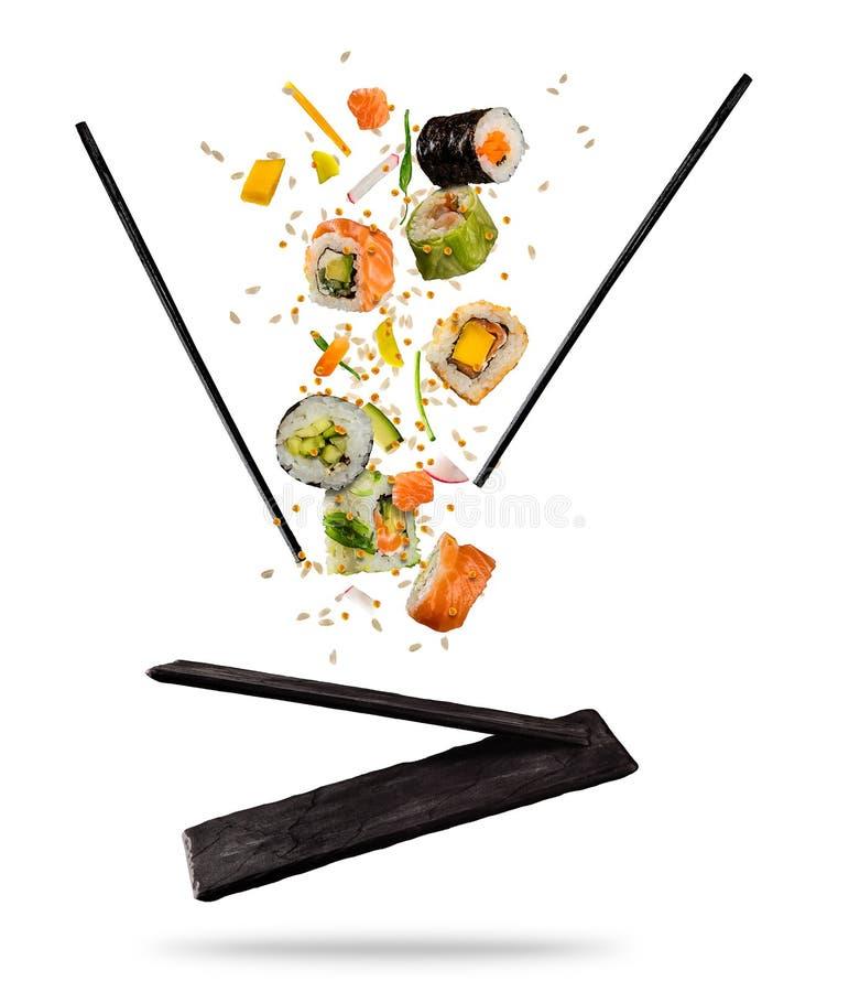 Het vliegen stukken sushi met houten eetstokjes en steenplaat, I stock fotografie