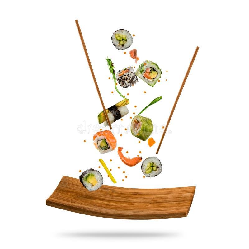 Het vliegen stukken sushi met houten eetstokjes en steenplaat, I stock afbeelding
