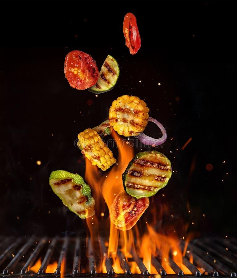 Het vliegen stukken van groente van grillnet, op zwarte bedelaars worden geïsoleerd die royalty-vrije stock afbeelding