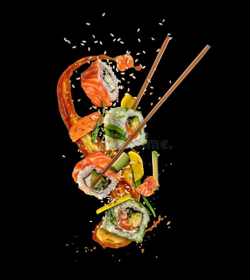 Het vliegen sushistukken op zwarte achtergrond stock afbeelding