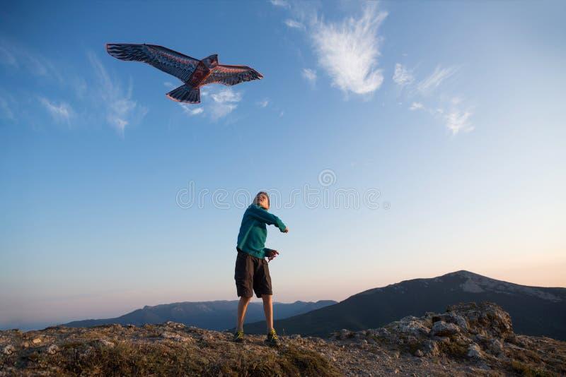 Het vliegen van de vlieger De jongen lanceert een vlieger Mooie Zonsondergang Bergen, overzees, landschap Zonnige de zomerdag royalty-vrije stock foto's