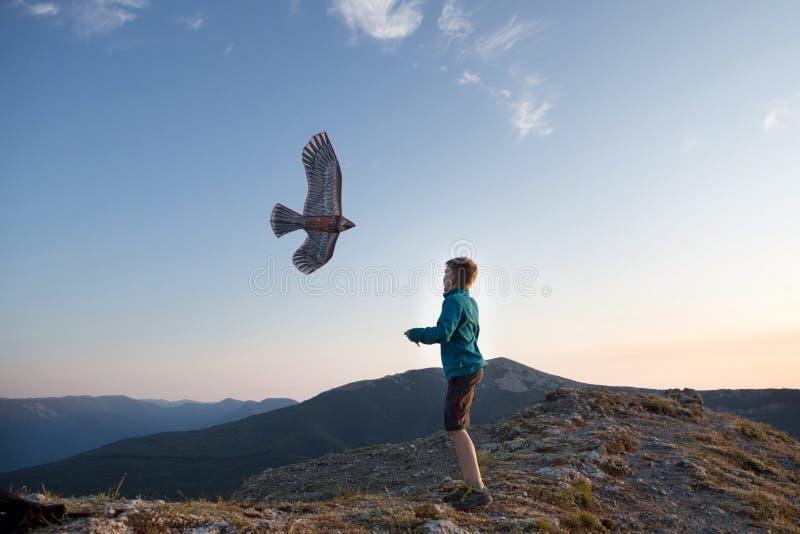 Het vliegen van de vlieger De jongen lanceert een vlieger Mooie Zonsondergang Bergen, overzees, landschap Zonnige de zomerdag stock foto's