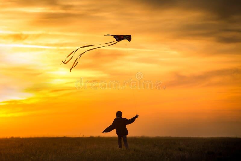 Het vliegen van een vlieger De jongenslooppas over het gebied met een vlieger Heldere, oranje zonsondergang stock foto's
