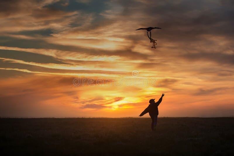 Het vliegen van een vlieger De jongenslooppas over het gebied met een vlieger Heldere Zonsondergang stock afbeelding