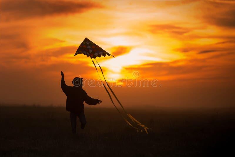 Het vliegen van een vlieger De jongenslooppas over het gebied met een vlieger Silhouet van een kind tegen de hemel Heldere Zonson stock afbeeldingen