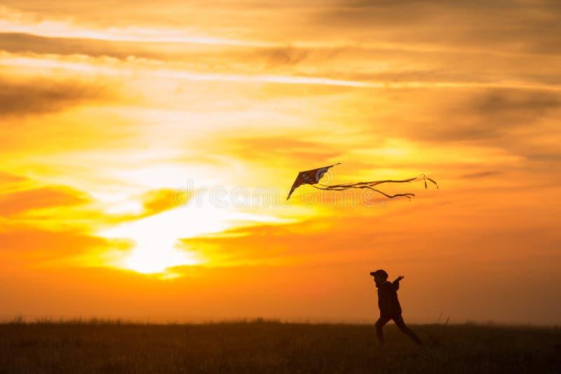Het vliegen van een vlieger De jongenslooppas over het gebied met een vlieger Silhouet van een kind tegen de hemel Heldere Zonson stock afbeelding
