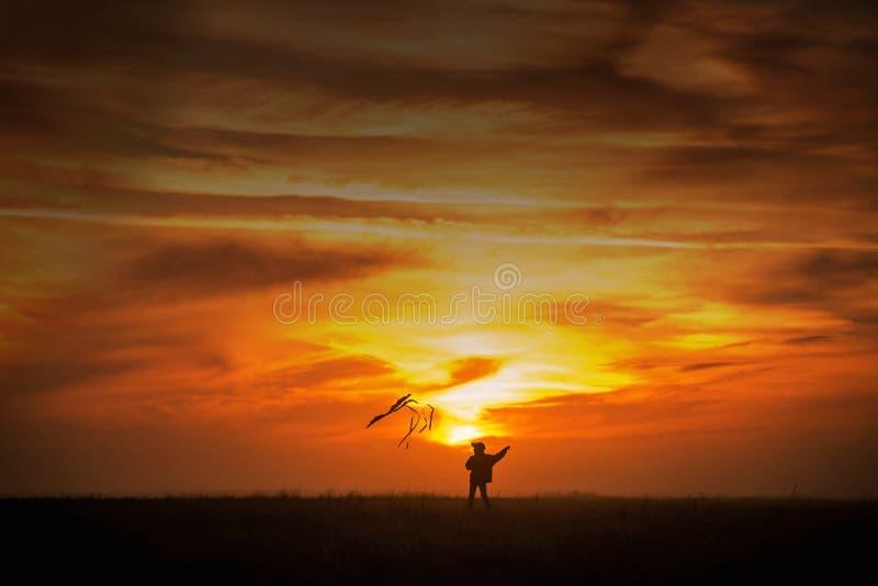 Het vliegen van een vlieger De jongenslooppas over het gebied met een vlieger Silhouet van een kind tegen de hemel Heldere Zonson royalty-vrije stock fotografie