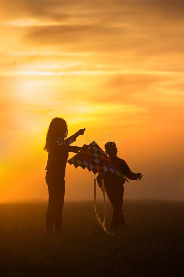Het vliegen van een vlieger Het meisje en de jongen vliegen een vlieger op het eindeloze gebied Heldere Zonsondergang Silhouetten royalty-vrije stock afbeeldingen