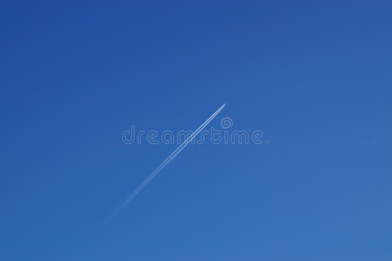 Het vliegen van het vliegtuig in de wolkenloze blauwe hemel stock foto