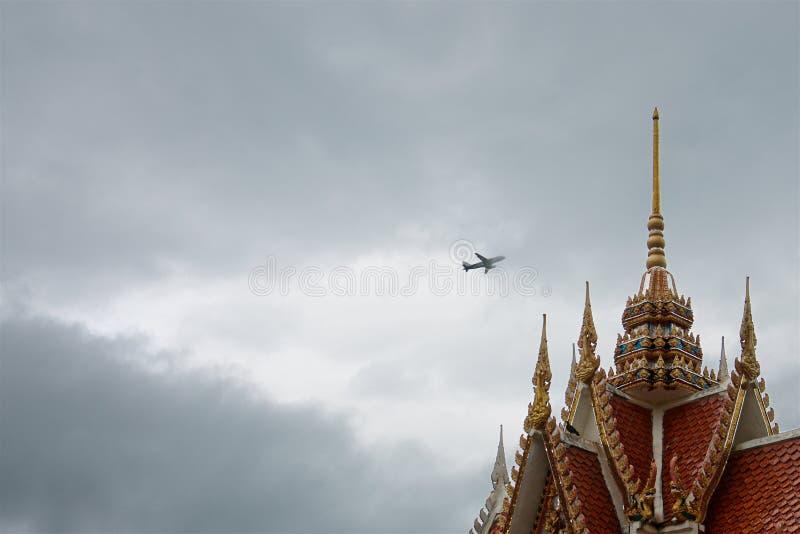 Het vliegtuig in de onweerswolken over het dak van een kleurrijke oude Thaise tempel stock afbeelding